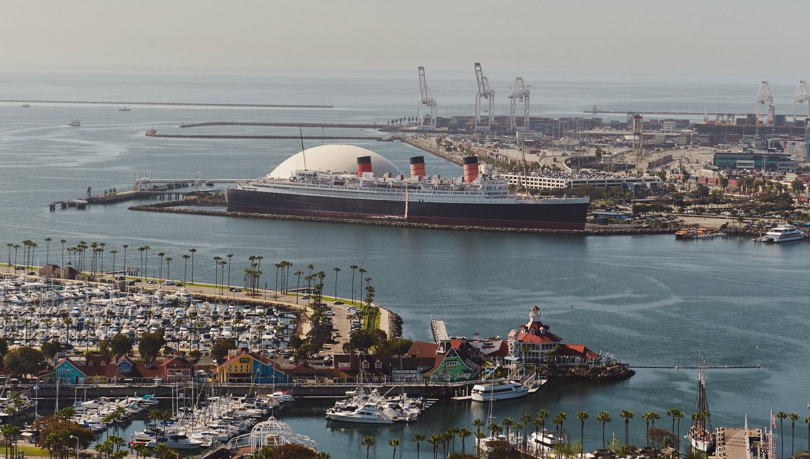 Queensway Bay in Long Beach, Calif., with the Queen Mary and docks in the distance. A $250 million entertainment and hotel complex is planned for the waterfront next to the Queen Mary. Credit Jake Michaels for The New York Times