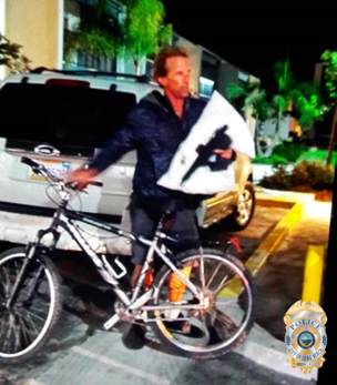 Photo of peeping Tom person of interest #2 standing with a bike